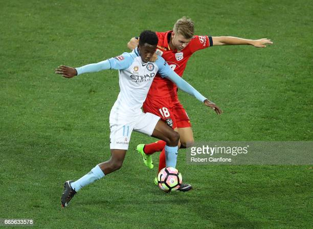 Bruce Kamau of Melbourne City is challenged by Riley McGree of United during the round 26 ALeague match between Melbourne City FC and Adelaide United...