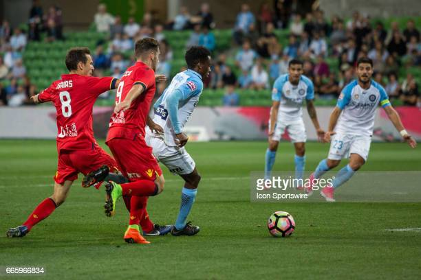 Bruce Kamau of Melbourne City runs with the ball with Isaias of Adelaide United and Papa Babacar Diawara of Adelaide United in close pursuit during...