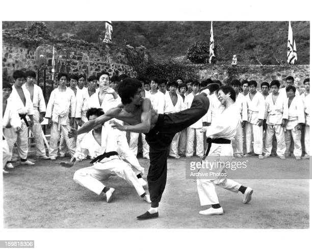 Bruce Lee practicing martial arts with a group of students in a scene from the film 'Enter The Dragon' 1973