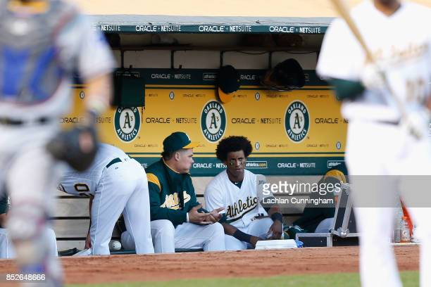 Bruce Maxwell of the Oakland Athletics chats to Khris Davis of the Oakland Athletics between innings of the game against the Texas Rangers at Oakland...