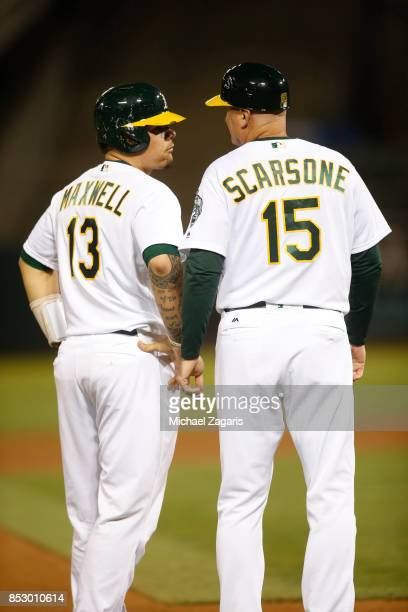Bruce Maxwell and Acting Third Base Coach Steve Scarsone of the Oakland Athletics talk at third base during the game against the Houston Astros at...