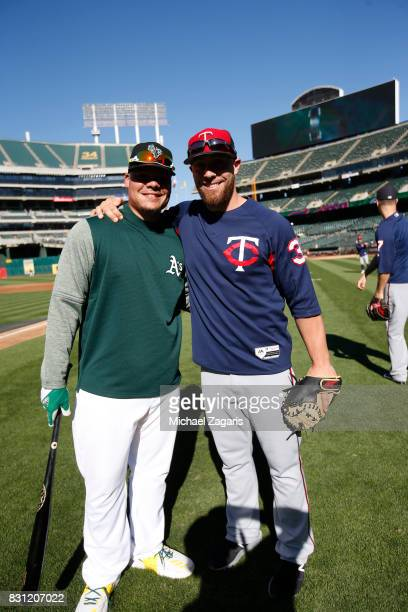 Bruce Maxwell of the Oakland Athletics and Chris Gimenez of the Minnesota Twins stand on the field prior to the game at the Oakland Alameda Coliseum...