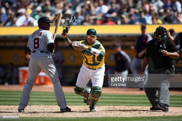 Bruce Maxwell of the Oakland Athletics chases down a wild pitch by Andrew Triggs of the Oakland Athletics while Justin Upton of the Detroit Tigers is...