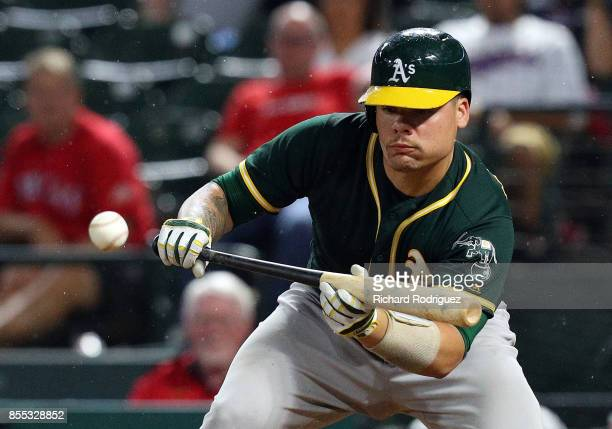 Bruce Maxwell of the Oakland Athletics hits a sacrifice bunt in the ninth innign of a baseball game against the Texas Rangers at Globe Life Park in...