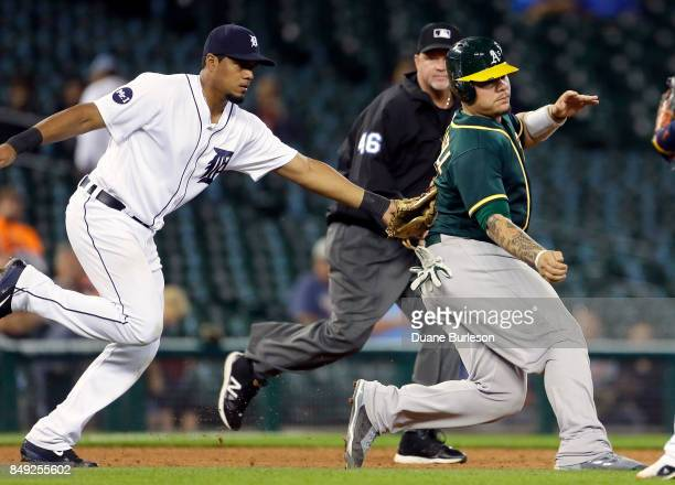 Bruce Maxwell of the Oakland Athletics is tagged out by third baseman Jeimer Candelario of the Detroit Tigers after getting caught in a rundown...