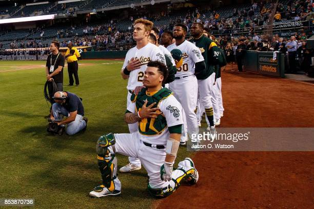 Bruce Maxwell of the Oakland Athletics kneels during the national anthem in front of teammate Mark Canha before the game against the Seattle Mariners...