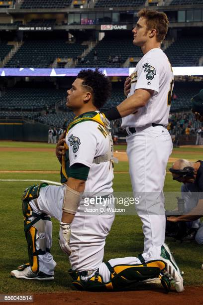 Bruce Maxwell of the Oakland Athletics kneels during the national anthem in front of Mark Canha before the game against the Seattle Mariners at the...