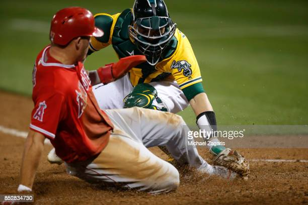 Bruce Maxwell of the Oakland Athletics tags Mike Trout of the Los Angeles Angels of Anaheim out at home during the game at the Oakland Alameda...