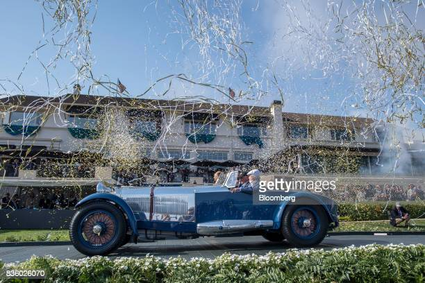 Bruce McCaw drives his 1929 MercedesBenz S Barker Tourer through falling confetti into the winners' circle to accept the Best of Show award during...