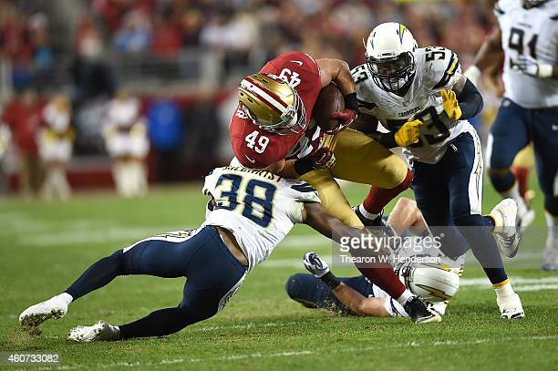 Bruce Miller of the San Francisco 49ers is tackled by Marcus Gilchrist and Kavell Conner of the San Diego Chargers at Levi's Stadium on December 20...