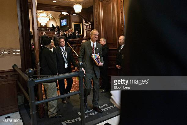 Bruce Rauner governor of Illinois center leaves the House Chamber at the State Capitol building after delivering a budget address in Springfield...