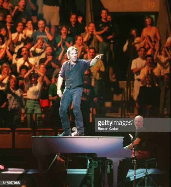 Bruce Springsteen stands atop a piano during his performance at the Fleet Center in Boston on Aug 27 1999