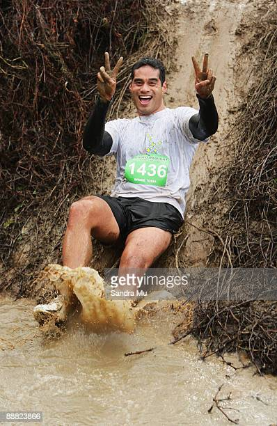 Bruce Togia of the North Shore slides down the mudslide into the stream during the Tough Guy and Gal multi sport race at Ti Papa Equestrian And...