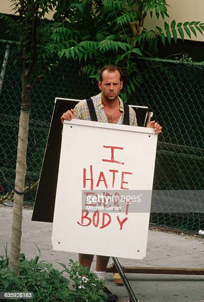 Bruce Willis holds a sandwich board with the message 'I hate everybody' written on it on the set of Die Hard With a Vengeance