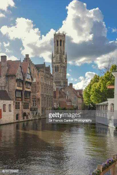 Bruges Belfry and Rozenhoedkaai canal with dramatic sky in Flanders, Belgium