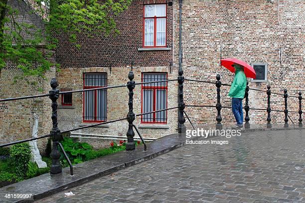 Bruges Belgium Flanders Europe Brugge woman with red umbrella in rain on bridge by Begijnhof nunnery