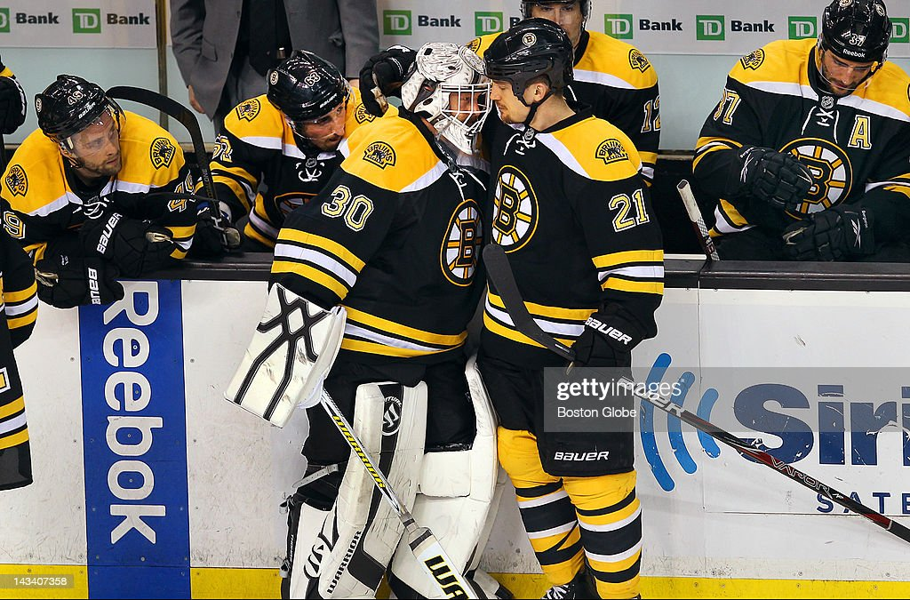 Bruins Andrew Ference gives a hug to goalie Tim Thomas at the end of the game as other Bruins sit dejected. The Boston Bruins and Washington Capitals met for game seven of the Stanley Cup Eastern Conference quarterfinals at TD Garden.