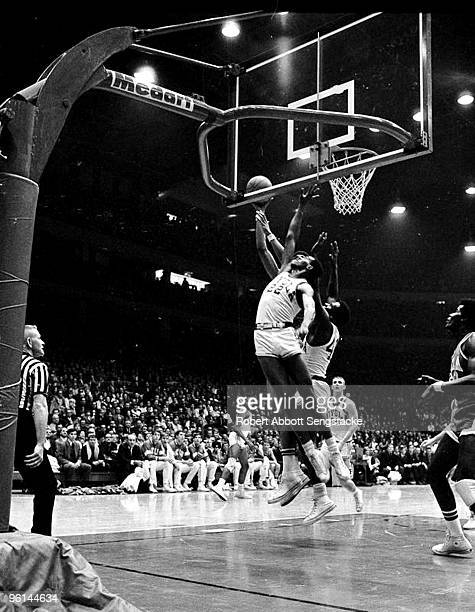 Bruins center Lew Alcindor now known as Kareem Abdul Jabbar is obscured behind two opposing players as he battles for the rebound in a game against...