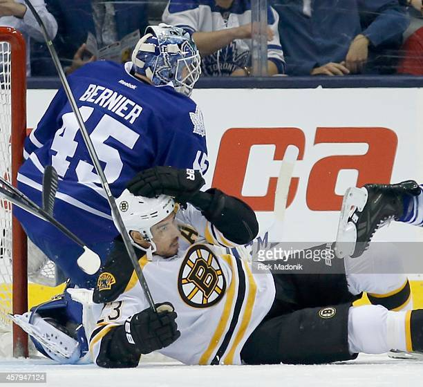 TORONTO OCTOBER 25 Bruins Chris Kelly gets levelled in front of Leaf goalie Jonathan Bernier Toronto Maple Leafs vs Boston Bruins during 1st period...