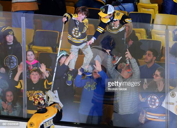 Bruins fans are held up against the glass at the end of the game as one is lucky enough to get a stick from Bruins goalie Tuukka Rask The Boston...