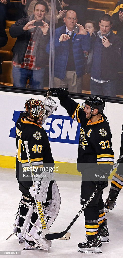 Bruins goalie Tuukka Rask, left, who stopped the last shot of the shootout, and teammate Patrice Bergeron, right, who scored the winning goal in the shootout, celebrate together as fans record the moment following the game. The Boston Bruins hosted the Winnipeg Jets in an NHL regular season game at the TD Garden.