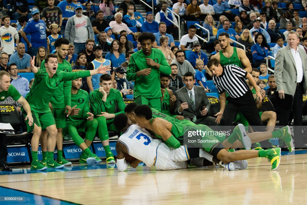 Bruins guard Aaron Holiday (3) and several Oregon Ducks players fight for a loose ball as the Oregon Ducks bench reacts during the game between the Oregon Ducks and the UCLA Bruins on February 17, 2018, at Pauley Pavilion in Los Angeles, CA.