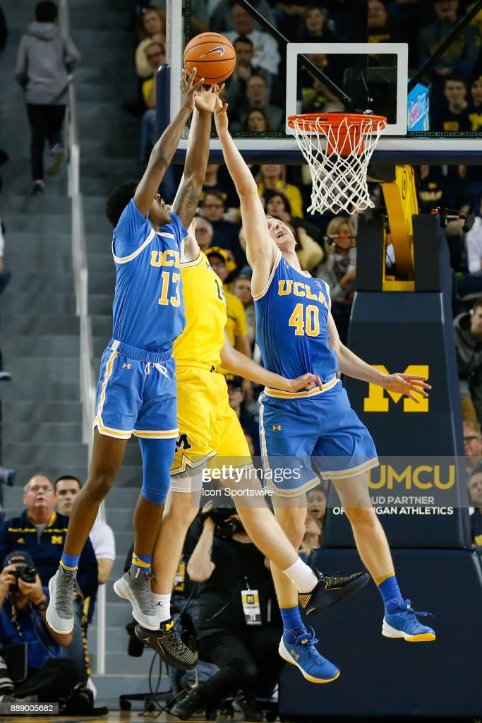 Bruins guard Kris Wilkes (13) and UCLA Bruins center Thomas Welsh (40) battle to grab a rebound against Michigan Wolverines center Jon Teske (15) during the second half of a regular season non-conference basketball game between the UCLA Bruins and the Michigan Wolverines on December 9, 2017 at the Crisler Center in Ann Arbor, Michigan. Michigan defeated UCLA 78-69 in overtime.