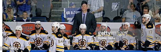 Bruins head coach Claude Julien and his team watch the replay of the third Tampa Bay goal of the second period that tied the game at 33 The Boston...