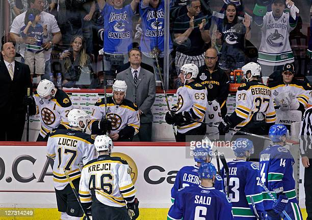 Bruins head coach Claude Julien far left and his players are pictured after the Canucks Daniel Sedin beat Bruins goalie Tim Thomas in the third...