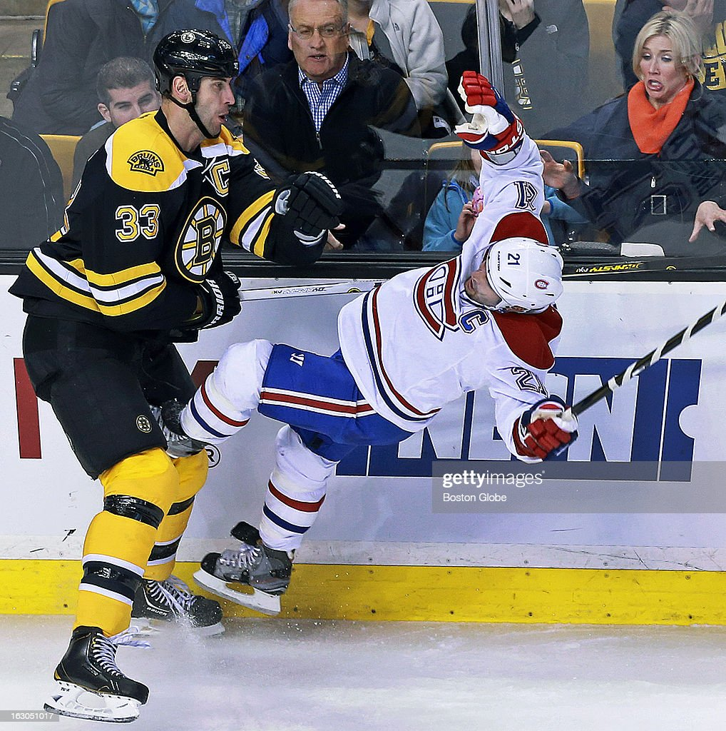 Bruins massive defenseman and team captain Zdeno Chara, left, sends diminutive Montreal winger, and fellow captain Brian Gionta to the ice with a hard first period hit. A fan at right recoils as she watches the action. The Boston Bruins hosted the Montreal Canadiens in a regular season NHL hockey game at the TD Garden.