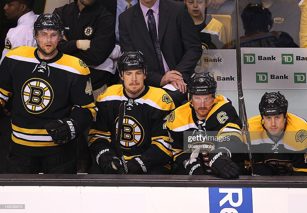 Dennis Seidenberg, Andrew Ference, Greg Zanon, and Joe Corvo, look downcast as they react to the Capitals third period goal.