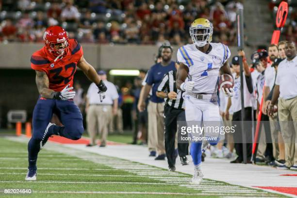 Bruins running back Soso Jamabo runs with the ball while Arizona Wildcats defensive end DeAndre' Miller tries to track him down during a college...