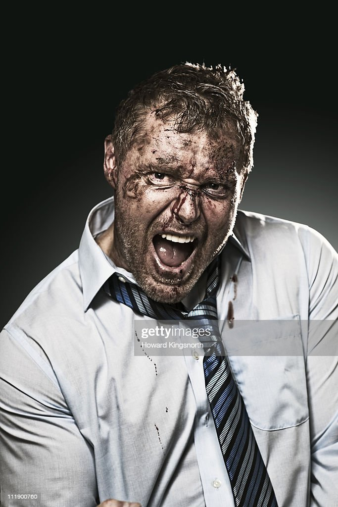 bruised and bloodied businessman, looking defiant : Stock Photo