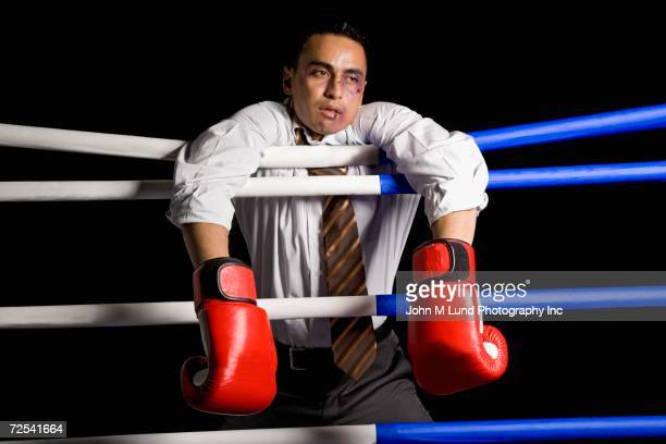 Bruised businessman hanging on ropes in boxing ring