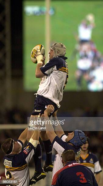 Brumbies lock David Giffen is mirrored in the big screen image as he is lifted in the lineout by Patricio Noriega left and Justin Harrison during the...