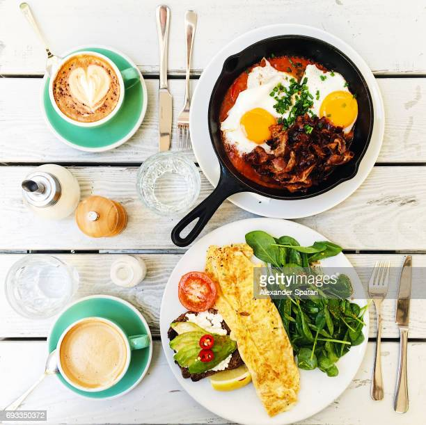 Brunch with fried eggs, bacon, omelet and avocado on toast served on the table, high angle view