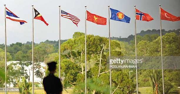 A Brunei policeman stands in front of flags from the Southeast Asian Nations countries and its dialogue partners at the end of ASEAN Foreign...