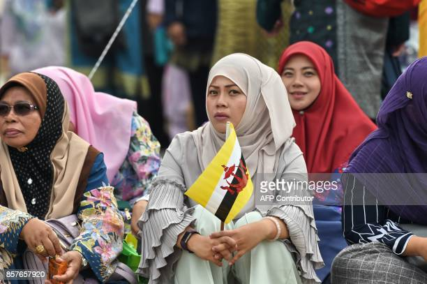 Bruneians sit along a roadside waiting for Brunei's Sultan Hassanal Bolkiah to ride past on a royal chariot during a procession to mark his golden...