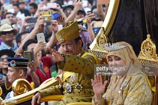 Brunei's Sultan Hassanal Bolkiah and Queen Saleha ride in a royal chariot during a procession to mark his golden jubilee of accession to the throne...