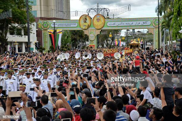 Brunei's Sultan Hassanal Bolkiah and Queen Saleha ride on the royal chariot during a procession to mark his golden jubilee of accession to the throne...