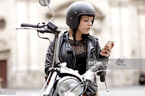 Brunette female posing on motorbike in old european city centre