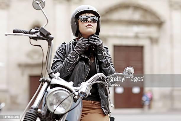 Brunette female posing on motorbike in old european city centre
