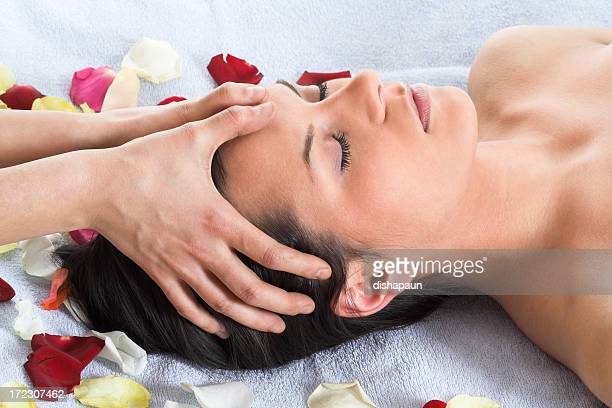 Brunette getting a head massage laying on a white towel