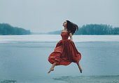 Beautiful brunette girl jumping, walking in the air. Background shore of a frozen river. She is wearing a beautiful orange dress. Sad face with a glimmer of hope to escape from the routine of everyday