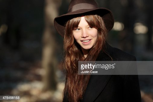 brunette girl with hat standing in forest light : Stock Photo
