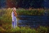 Brunette in viking dress by river at dusk