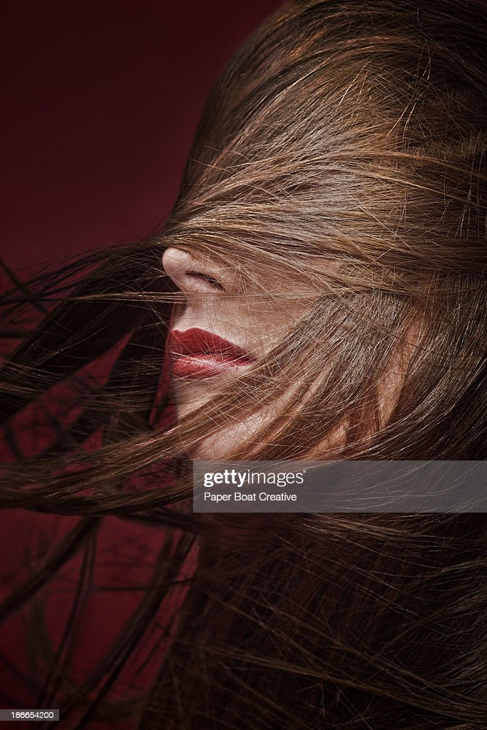 Brunette lady with hair sweeping around her : Stock Photo
