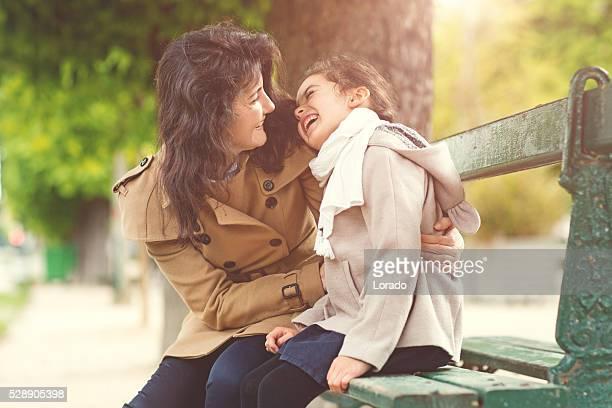 Brunette mother daughter hugging in Paris park on spring afternoon