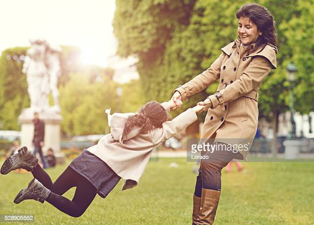 Brunette mother daughter playing in Paris park on spring afternoon