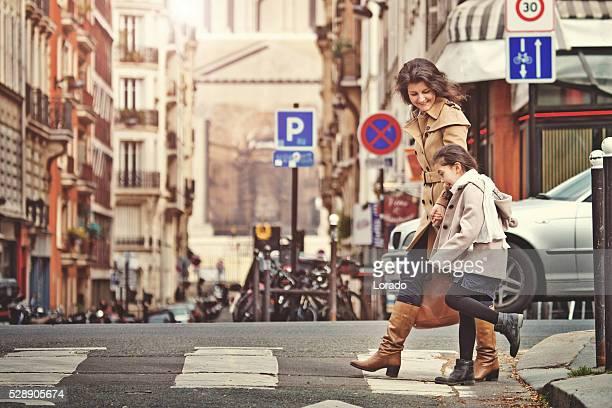 Brunette mother daughter walking in Paris streets on spring afternoon